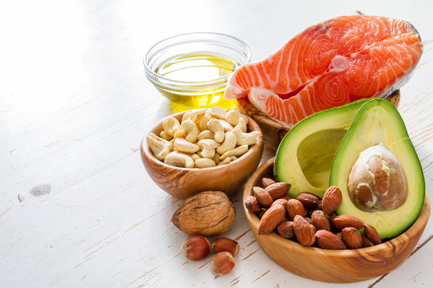 Selection of healthy fat sources, nuts, oils, avocado and salmon